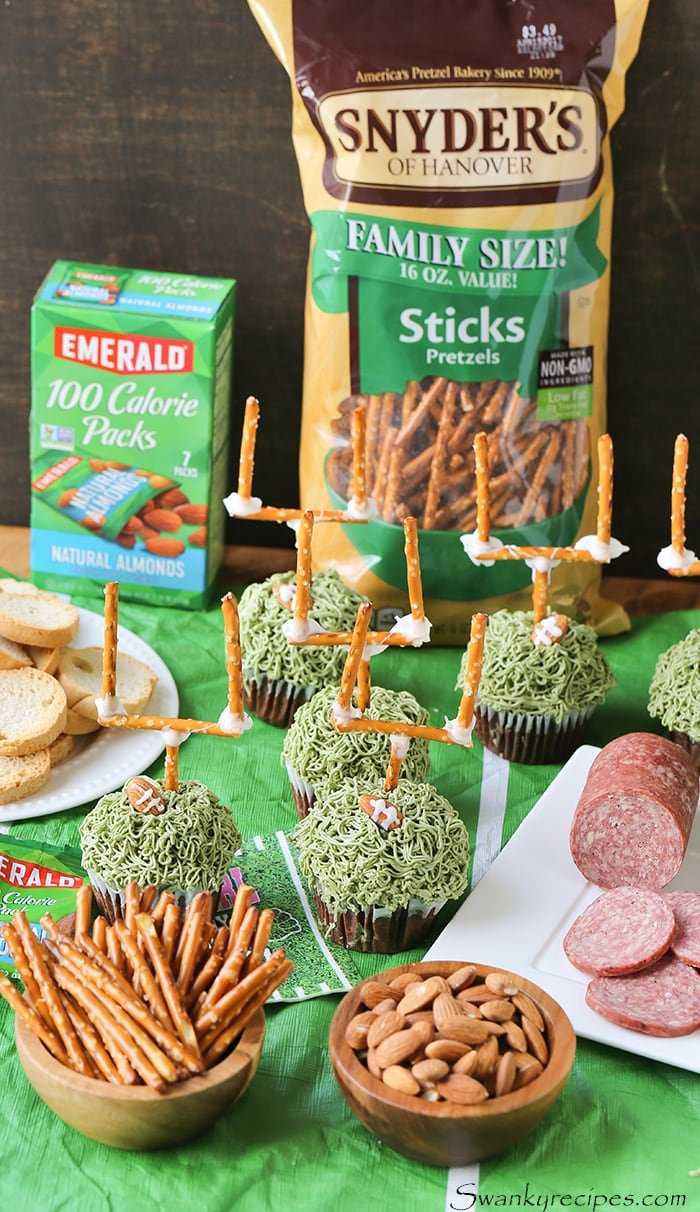 Kick off the football championship with Football Touchdown Cupcakes. Rich chocolate cupcakes with green frosting, frosted almonds and a pretzel stick touchdown. Make this for the next game day party.