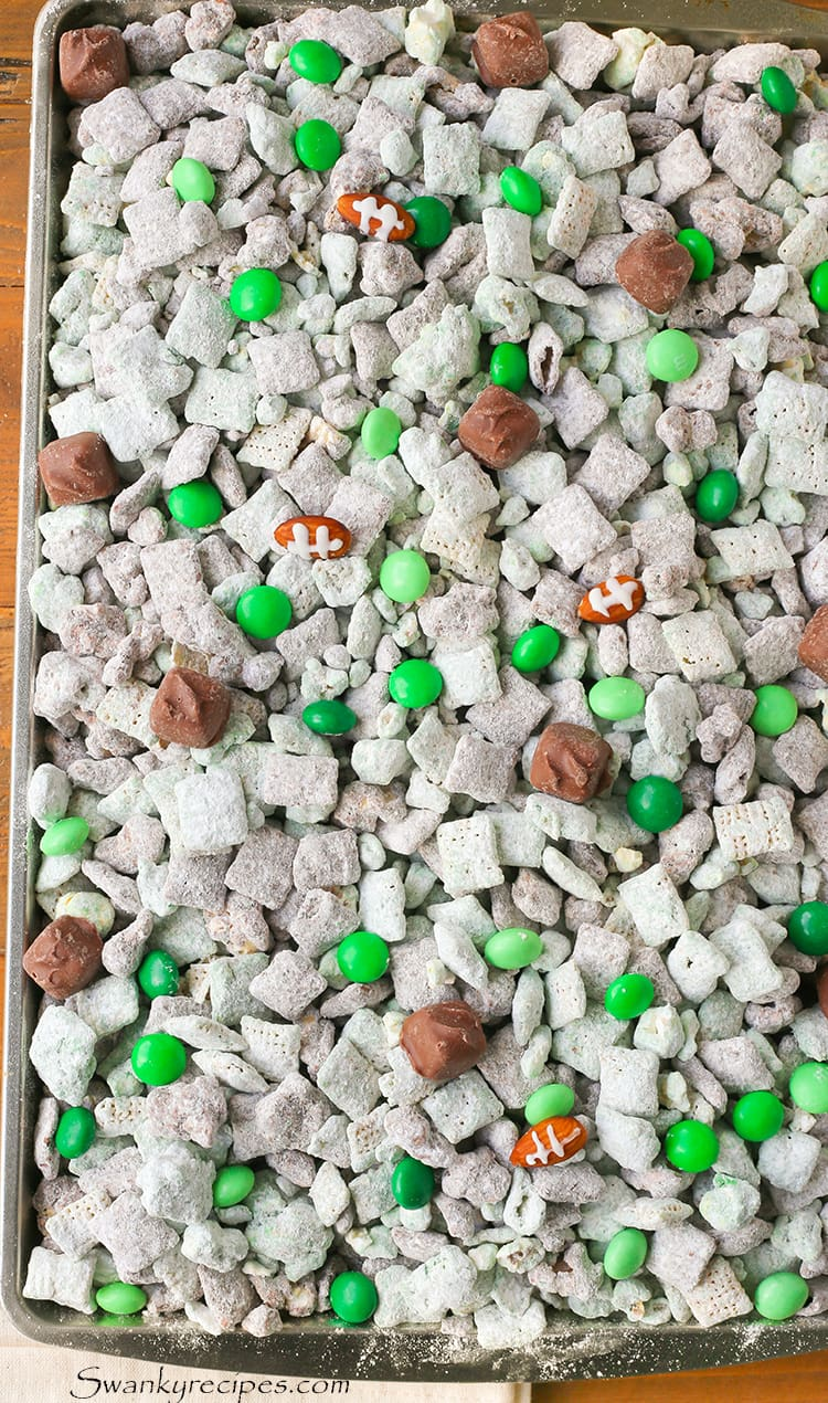Mint Chocolate Football Puppy Chow - Everyone's favorite game day snack made with rice cereal, popcorn, chocolate, mint and chocolate candy pieces.