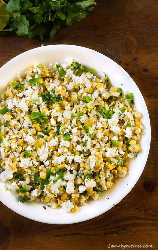 Mexican Street Corn Salad - Fresh corn kernels charred over fire and slathered in a cilantro lime cream sauce with feta cheese, onions and seasoning.  Serve as a side to any summer dish.