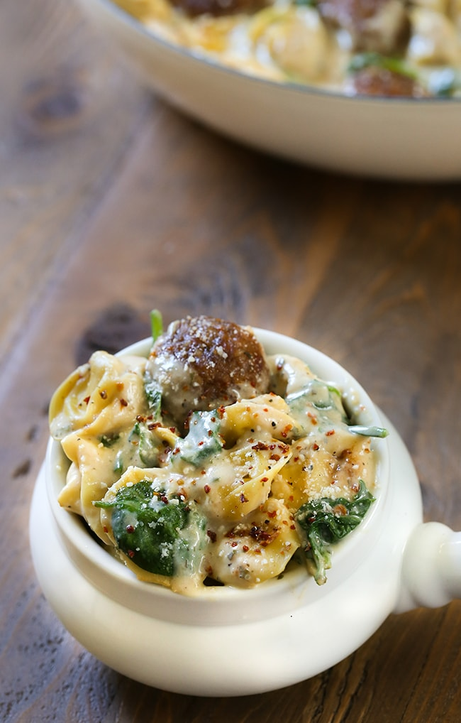 Creamy Spinach Tortellini Pasta with Meatballs - Pan seared garlic with a rich and flavorful creamy onion sauce with spinach, meatballs and tortellini pasta.  Pan tossed with parmesan cheese and herbs to give a robust Tuscan flavor.  A truly simple dish to make for dinner or to serve for a dinner party with a glass of wine.  This recipe will become a family favorite.