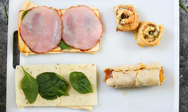 Ham and Cheese Pinwheels - Buttery, flaky, garlic butter crescent roll dough with melted cheese, baby spinach, cheese, and ham. These deli meat pinwheels are perfect for lunch!