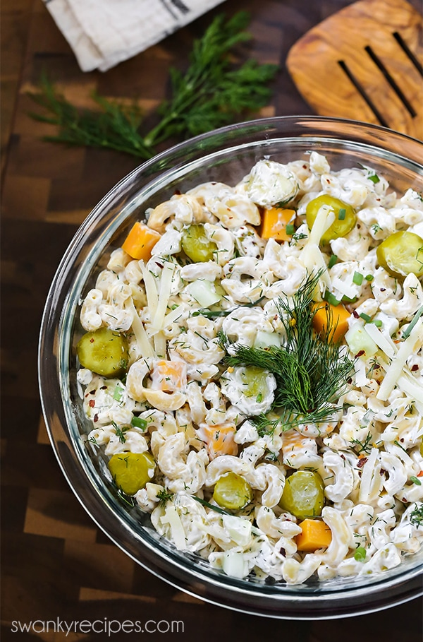 Toss the classic pasta salad ingredients together in a bowl with pickles, cold pasta, dill, and cheddar cheese.