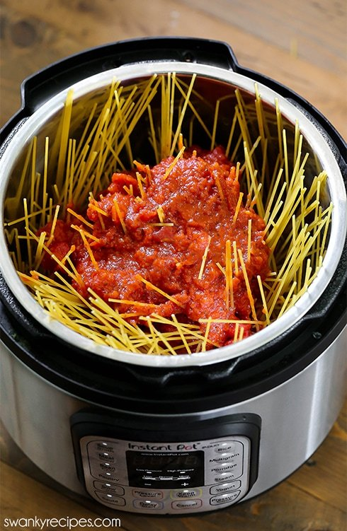 Spaghetti pasta noodles layered with tomato sauce in a instant pot pressure cooker with meat sauce.