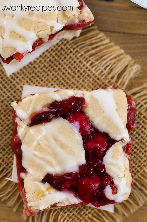 Cherry pie bar with a cookie bar crust recipe. Made with cherry pie filling baked in the oven and served with vanilla ice cream.