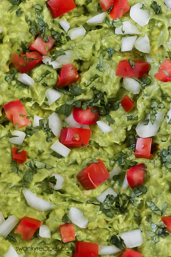 Guacamole is a Mexican staple served as a sauce, topping, spread, or dip. Made with fresh ingredients like white onion, cilantro, tomato, avocados, and lime juice. A close up of guacamole in a bowl.