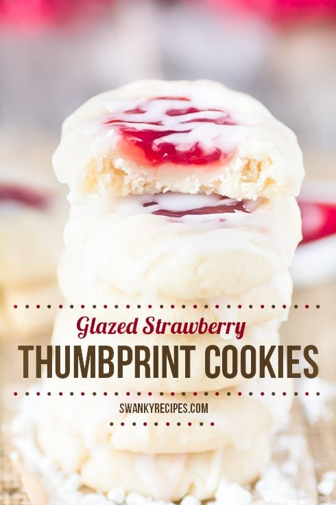 Classic Strawberry Jam Thumbprint Cookies stacked on burlap. each center of the cookie is filled with strawberry jam then icing in a powdered sugar icing glaze. Text on photo reads Glazed Strawberry Thumbprint Cookies.
