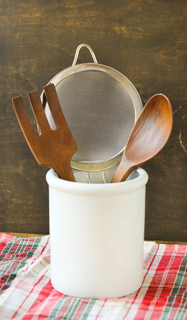A utensil holder, wooden serving set and fine mesh strainer.