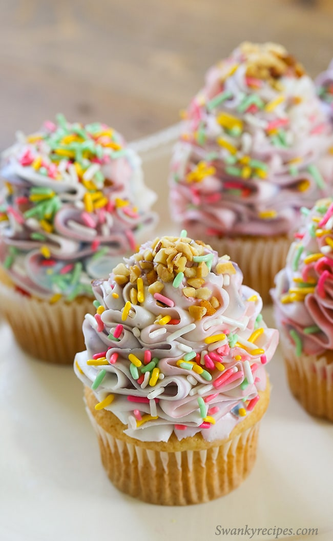 Unicorn Cupcakes - Cherry and almond cupcakes with beautiful purple, pink and blue swirled frosting. Topped with pastel sprinkles and nuts.