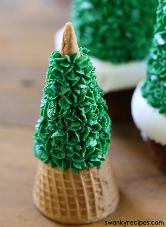Easy Christmas Tree Cupcakes with gingerbread cake, snowy frosting and an ice cream cup decorated with frosting. These Christmas cupcakes are perfect for the holiday season and are a lot of fun to make.