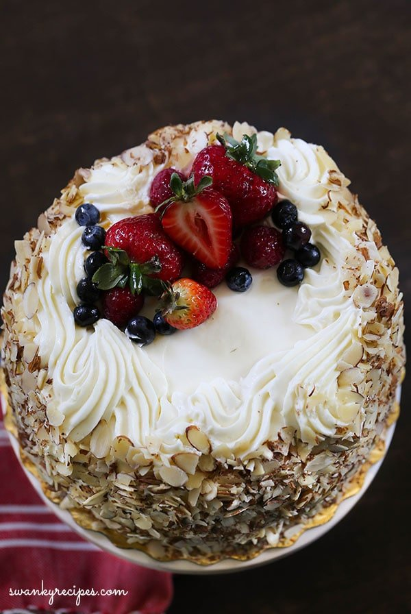 Berry Chantilly Layer Cake - The quintessential summer dessert. Layer upon layer of yellow cake filled with bakery style almond Chantilly Frosting, sliced strawberries, blueberries, and raspberries. If you love strawberry shortcake, you'll love this elevated summer holiday cake. #cake