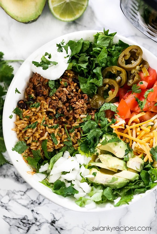 Easy Instant Pot Beef Taco Burrito Bowls. A one pot meal with ground beef, and rice. Topped with avocado, cilantro, lime, cheese, tomatoes, lettuce, and other traditional burrito bowl toppings. Taco bowls are served with tortilla chips and Queso Dip.