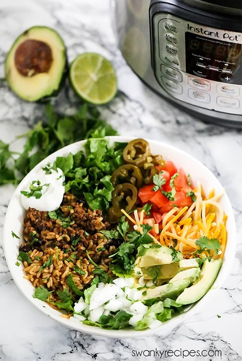 The BEST Instant Pot Taco Bowls - An easy weeknight dinner recipe cooked in one pot. These Tacos bowls have all the traditional Mexican fixings.
