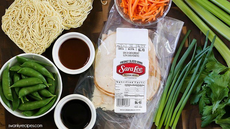 Korean Chicken Noodle Soup ingredients include: carrots, snow peas, celery, instant ramen noodles, diced chicken deli meat, green onions, Korean chili pasta, and soy sauce.
