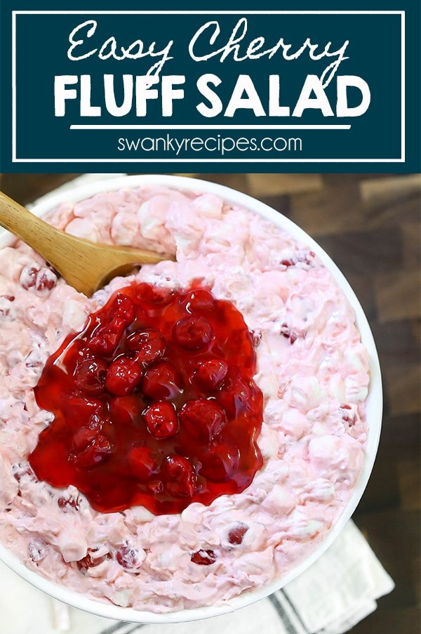 A spoon scooping into a bowl of cherry whipped cream marshmallows with cherry pie filling on top.