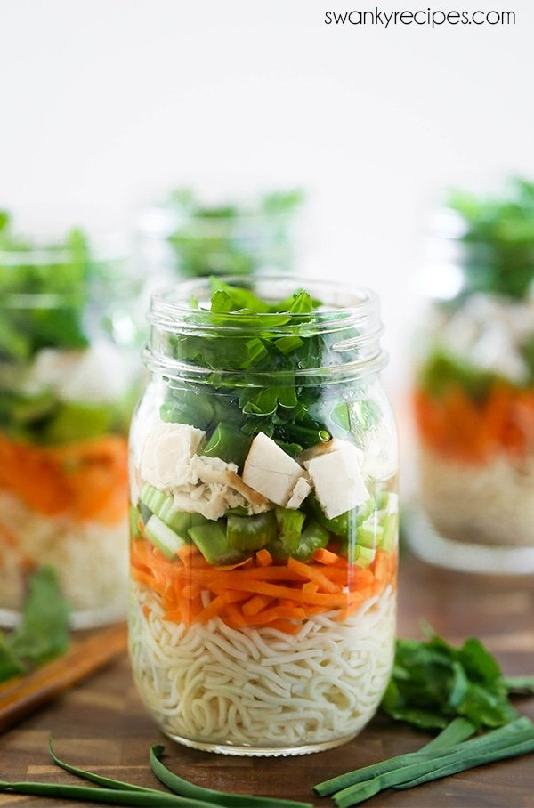 Hot water poured into mason jars with Chicken Noodle Soup ingredients.