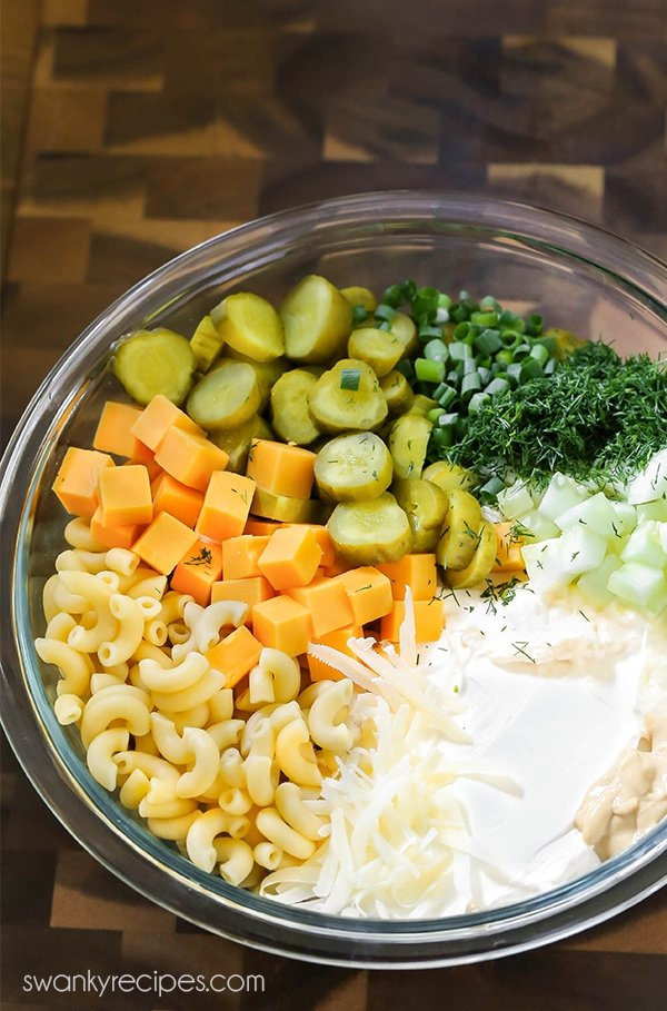 Pickle salad ingredients in a mixing bowl. Sour cream, mayo, sliced dill pickles, cucumbers, mustard, diced sharp cheddar cheese, cold pasta, and green onions.