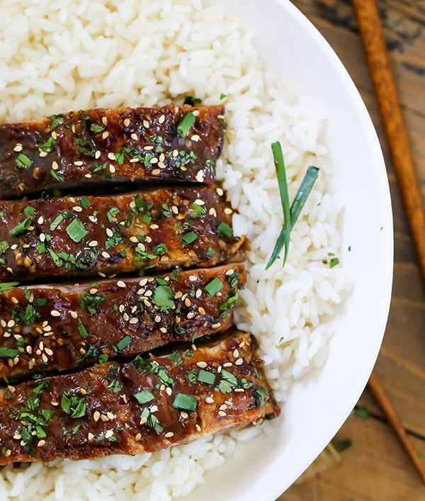 Pork ribs in a bowl with rice. A close up of baby back ribs cut and served on a bed of rice.