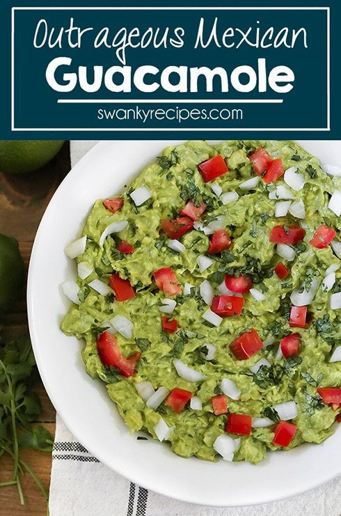 Real Guacamole Dip served in a bowl with tomato, onion, lime juice, cilantro, and garlic.