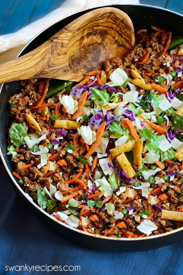 Egg Roll Bowls with ground chicken, shredded cabbage, carrots, snow peas, and fried wontons in a skillet.