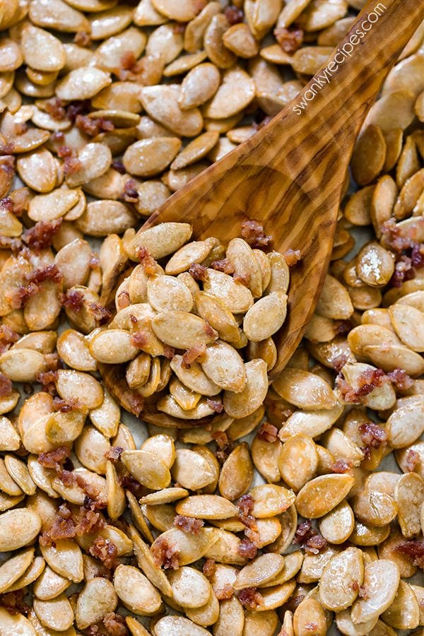 Maple Bacon Pumpkin Seeds - Quick and easy roasted pumpkin seeds. Sweet maple syrup and salty bacon tossed with pumpkin seeds for Halloween.