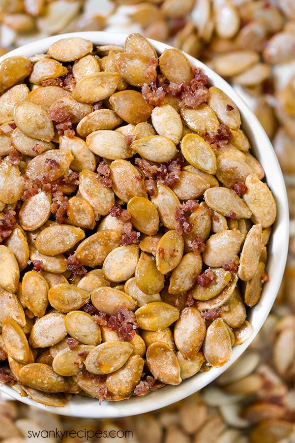Roasted Maple Pumpkin Seeds with bacon in a bowl. Topped with homemade bacon salt. Save those pumpkin seeds from your Halloween carved pumpkin and make this quick and easy snack recipe.