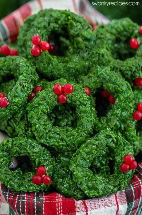 Christmas Corn Flake Wreath Cookies with green garland and cinnamon candies as bows.