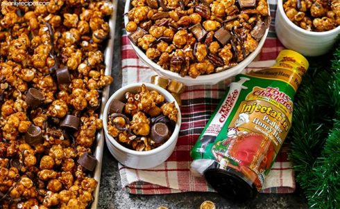 Christmas dessert table spread with bowls of caramel coated popcorn. Delicious Moose Munch with toffee, caramel, popcorn, and chocolate.