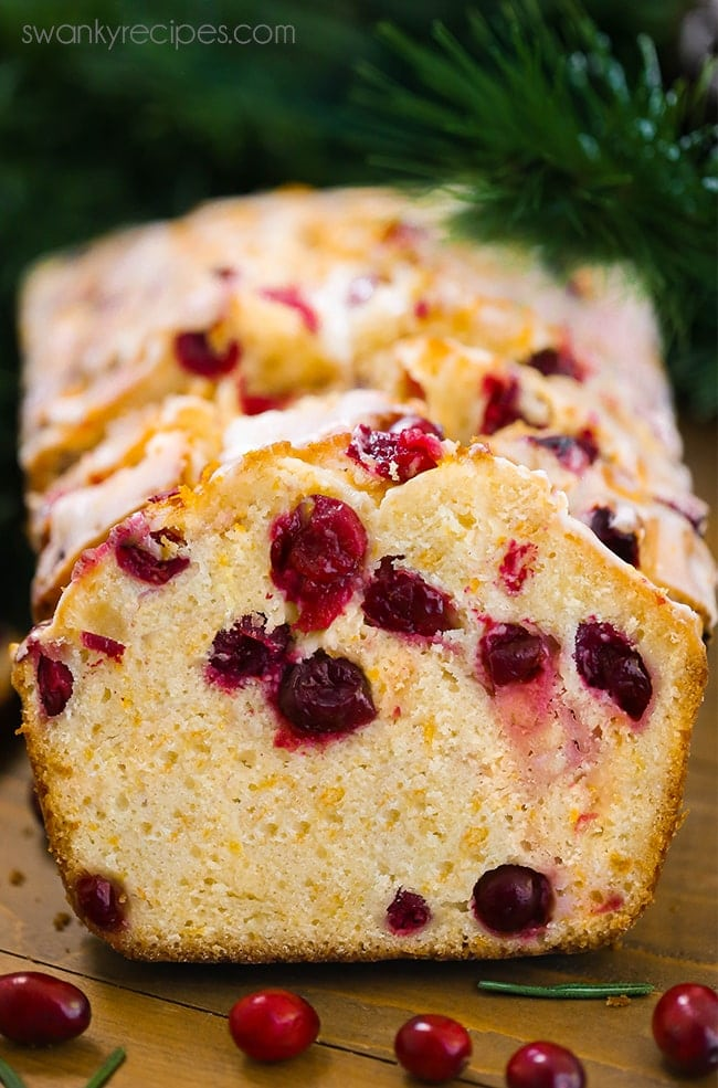 Slices of Cranberry Orange Bread with an orange icing glaze on top for the winter season.