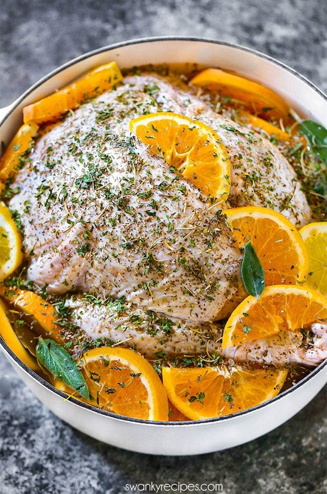 Turkey brining in salt water with citrus oranges and lemon. Fresh and dried herbs seasoning.