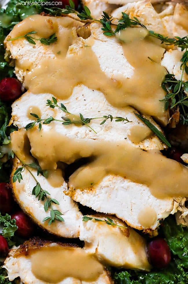 Roast Turkey drizzled in homemade turkey gravy on a plate with cranberries and salad. Juicy her butter turkey served for Thanksgiving dinner.