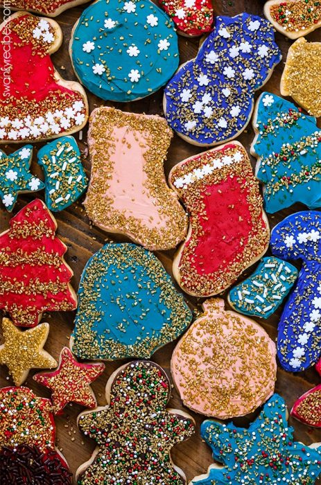 Christmas Sugar Cookie Cutouts with holiday shapes. Cookies covered in vibrant winter colors with gold sprinkles and cookie decorations.