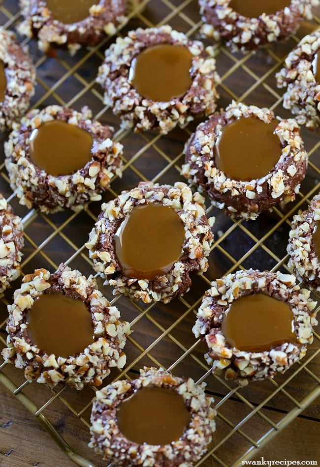 Turtle Thumbprint Cookies with chocolate cookie rolled in pecans and filled with caramel sauce.