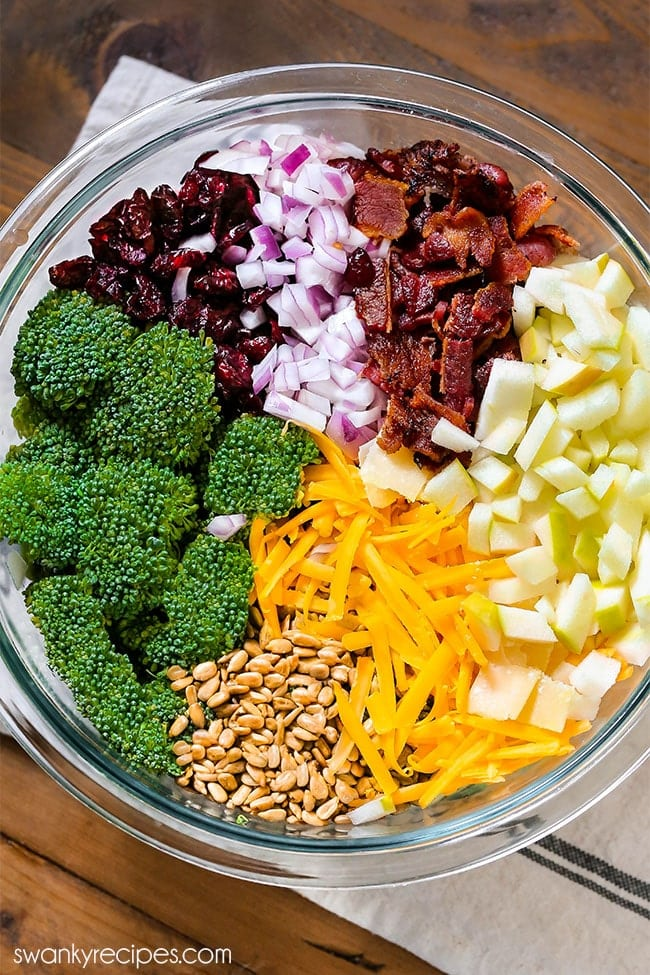 Broccoli Salad - The perfect side dish recipe made with broccoli florets, dried cranberries, bacon, cheese, onions, nuts, and apples. Tossed a a creamy homemade dressing with apple cider vinegar.