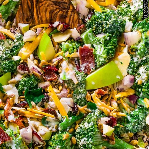 Broccoli Salad made with broccoli florets, dried cranberries, nuts, apple, bacon, cheddar cheese, and onions. Tossed in a creamy mayonnaise and sour cream dressing.