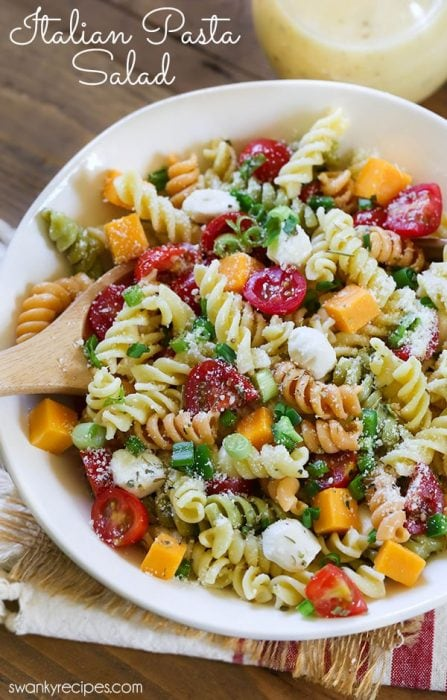 CLASSIC ITALIAN PASTA SALAD. This cold pasta salad is tossed in Italian dressing with bits of cheddar cheese, cherry tomatoes, jalapenos, mozzarella cheese balls, and green onions.
