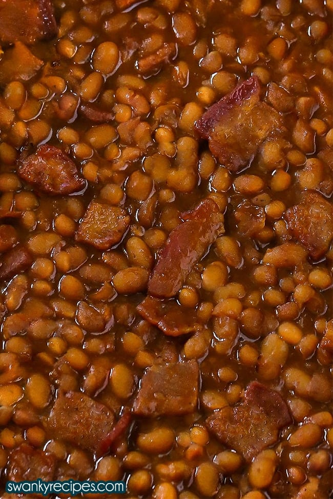 A close up of cooked beans in a thick brown sugar molasses sauce with pieces of bacon.