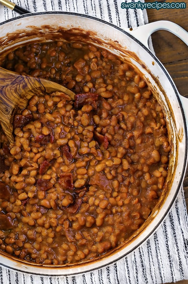 Baked Beans baked in a dutch oven. Scooped pieces of beans in a thick brown sauce with an olive wood spoon and bacon pieces.