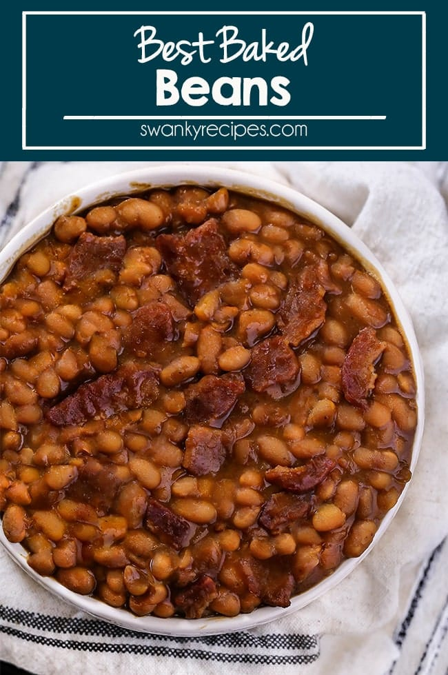 Cooked Baked Beans served in a small white bowl in a thick brown sauce with pieces of cooked bacon.
