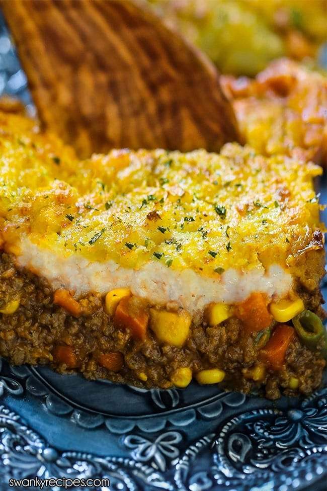 Ground beef casserole in a beef and tomato sauce with corn, peas, carrots, green beans, and mashed potato topping.