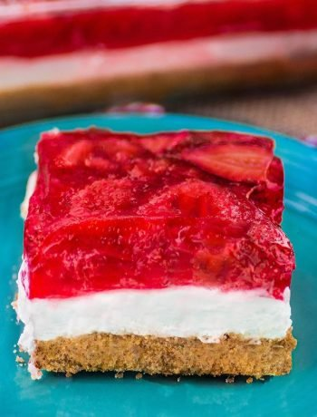 Strawberry Cheesecake Pretzel Dessert Salad. Blue plate with a thick square slice of dessert featuring a golden brown pretzel cookie crust with cheesecake filling in the center. topped with freshly sliced strawberries tossed with strawberry jello.