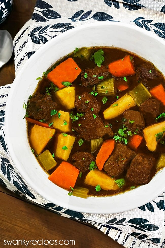 Slow Cooker Beef Stew - Beef stew served in a white soup bowl with a white and blue flower napkin on a wooden table. 10 pieces of browned chuck roast with a few pieces of orange carrots, yellow potatoes, and chopped celery. Garnished with chopped celery leaves.