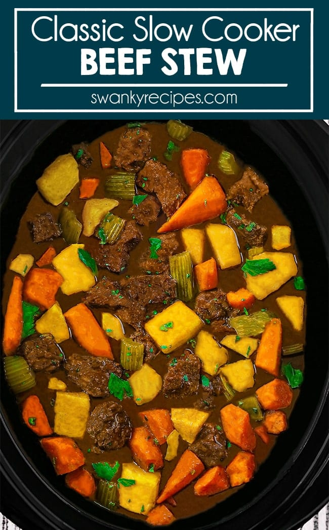 Slow Cooker Beef Stew with Vegetables - Image of beef stew fully displayed vertically in a black crock pot. A brown broth throughout with pieces of beef roast, potatoes, carrots, celery, and celery leaves.