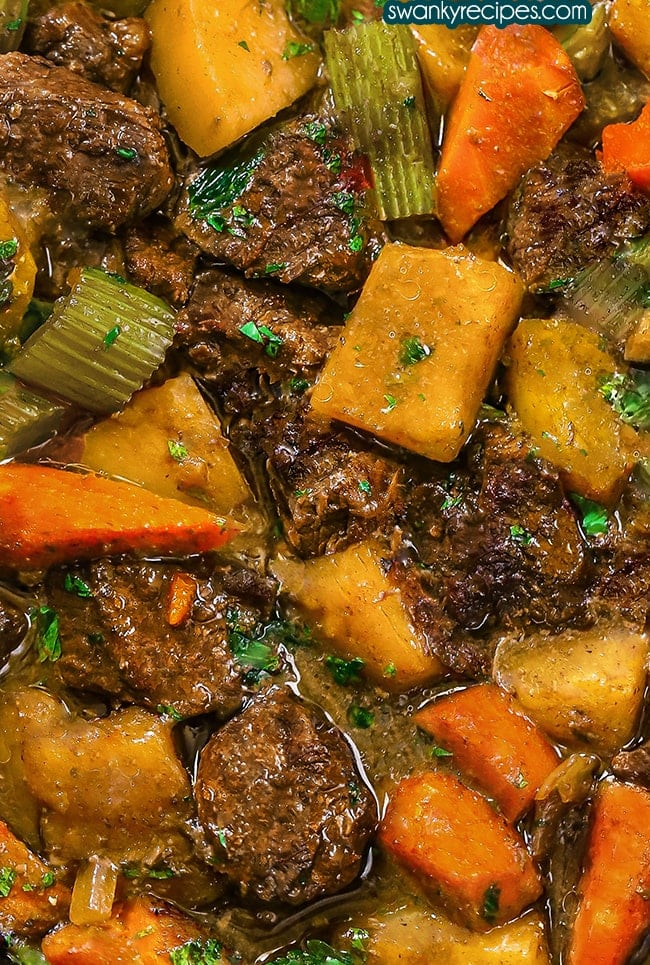 Crock Pot Beef Stew - Very close up image of beef chunks with diced potatoes, sliced carrots and celery in a yellow broth. Garnished with green celery leaves.