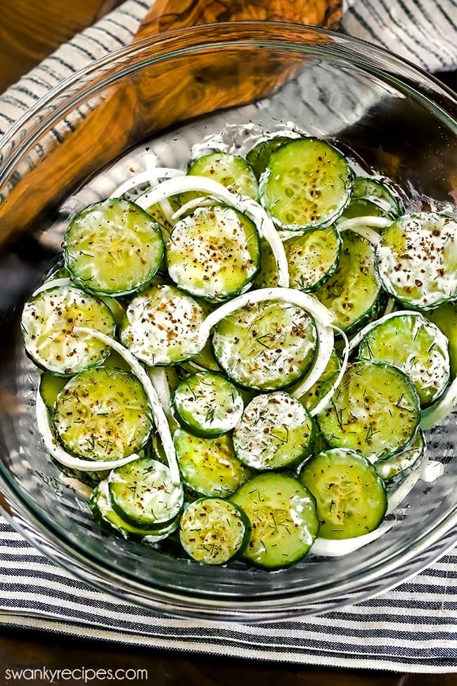 Sliced English cucumbers in a clear bowl with a thin sour cream white dressing, fresh peppercorn flakes on top with fresh dill and white onions scattered. Set on a wooden tabletop with a navy blue pinstripe napkin and a wooden spoon.