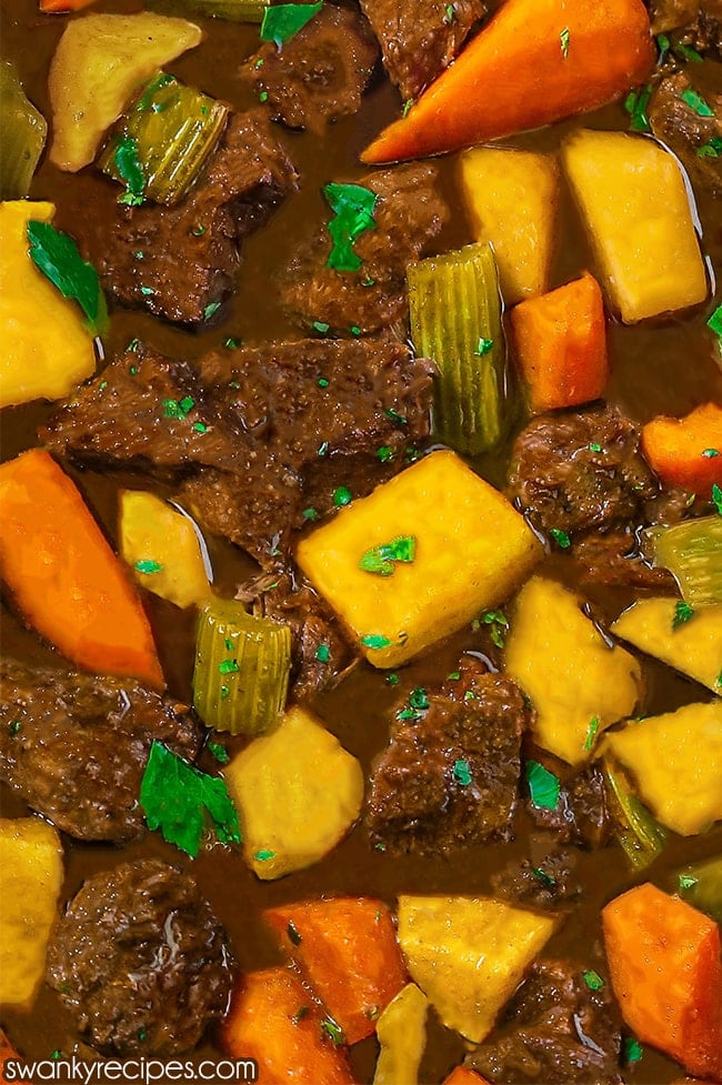 Best Crock Pot Beef Stew Recipe - Close up image of beef stew with pieces of chuck roast surrounded by yellow chunks of peeled potatoes, sliced and peeled carrots, and celery. Partially submerged in a brown gravy with chopped celery leaves sprinkled throughout the image.