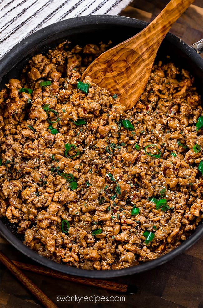 Ground chicken minced and cooked in a skillet. Tossed in a brown sauce using soy sauce, honey, garlic, sesame oil, and rice vinegar. Skillet served on wooden cutting board. Topped with diced green onions and sesame seeds with chopsticks below.
