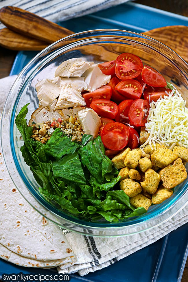 Chicken Caesar Salad Wraps text in white with purple background. Salad ingredients in a clear bowl on a blue platter with chopped lettuce, yellow croutons, shredded parmesan cheese, halved cherry tomatoes, and diced chicken with salad topping arranged in the bowl.