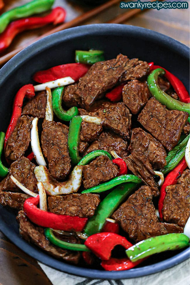 A slightly slanted top side view of a dark skillet with steak and peppers set on a white cloth napkin and wooden table. Skillet close up with stir fried red and green bell peppers and onions cut into strips sprinkled between golden brown beef strips. Tossed in a thick brown glaze. Wooden chopsticks behind the skillet with cut strips of red and green bell peppers.