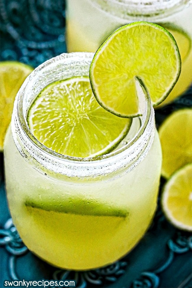 A close up of mason jars filled with blended tequila, triple sec, fresh lime juice, and ice. Topped with lime slices on the rim, top of glass and a lime in the glass cup. Rim is dusted with salt. Served on a blue platter with a margarita behind and lime slices.
