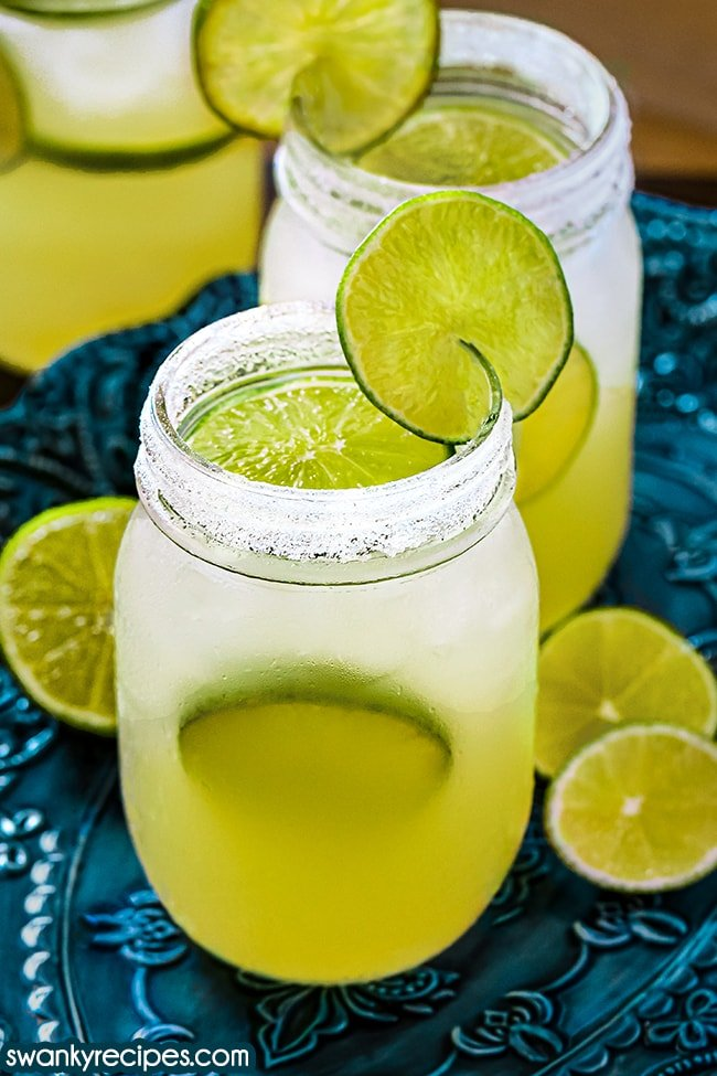 A front view of lime margaritas. Mason jars filled to the rim with margarita liquid. A yellow and frost white color. Mason jar rim dusted with salt and sugar. Topped with a ice and a lime slice. Lime slice in the cup and a lime slice on the rim. Served on a glass blue platter with lime halves behind the beverage.